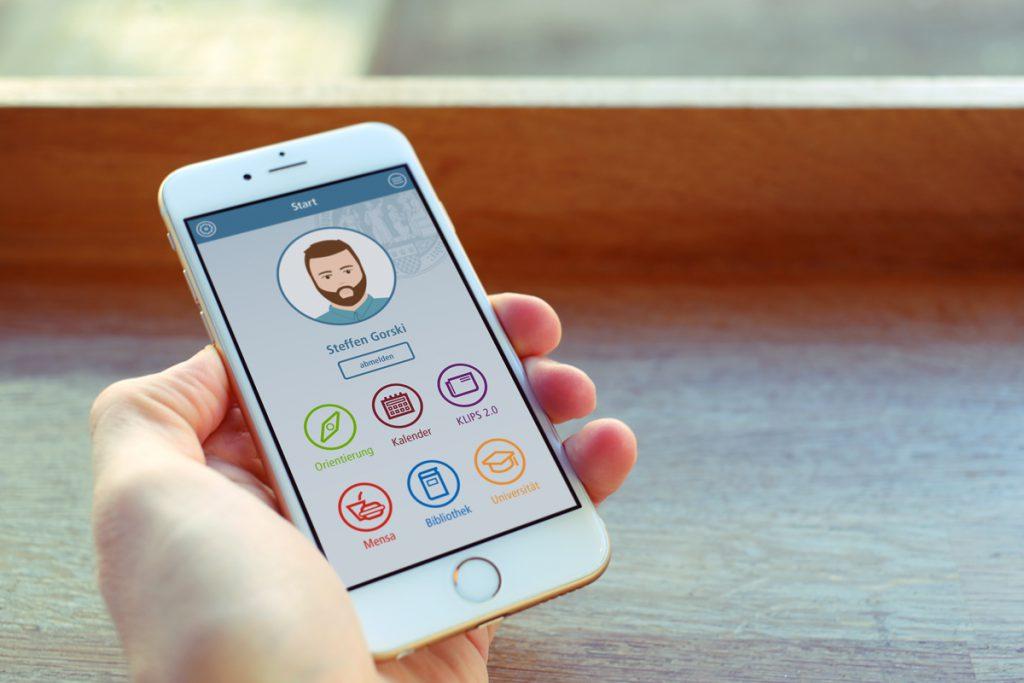 Hand mit Smartphone und Startbildschirm für eine App der Uni Köln